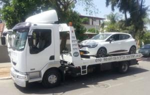 רכב לבן מועבר למגרש פירוק רכבים